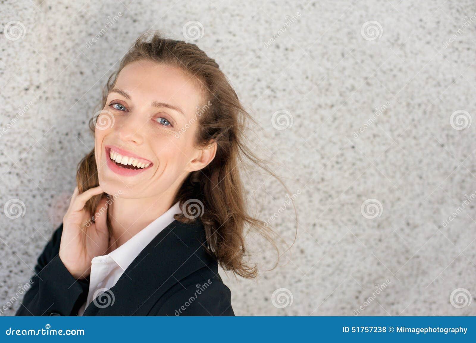 Счастливая бизнес-леди смеясь над выражающ позитивность