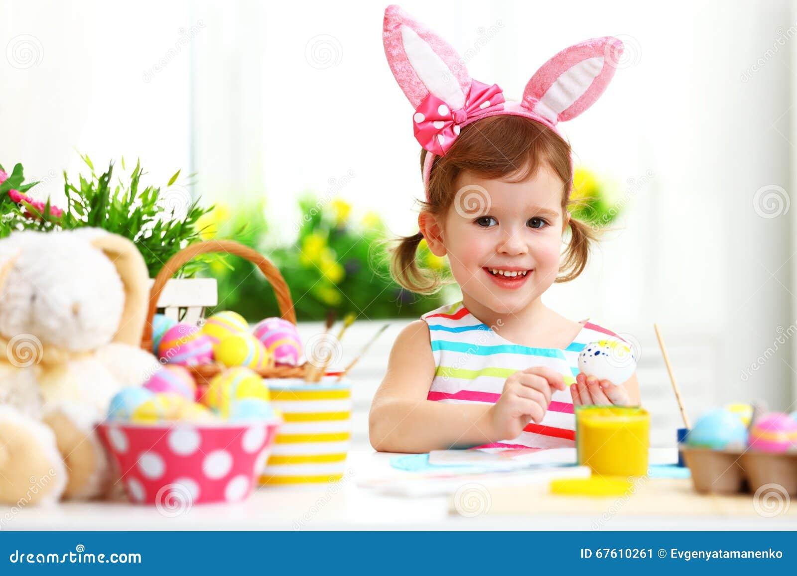 Счастливая девушка ребенка красит яичка для пасхи