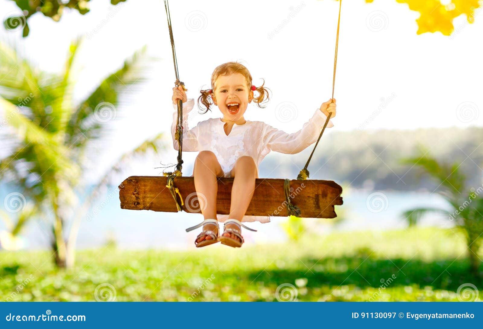 Счастливая девушка ребенка отбрасывая на качании на пляже в лете