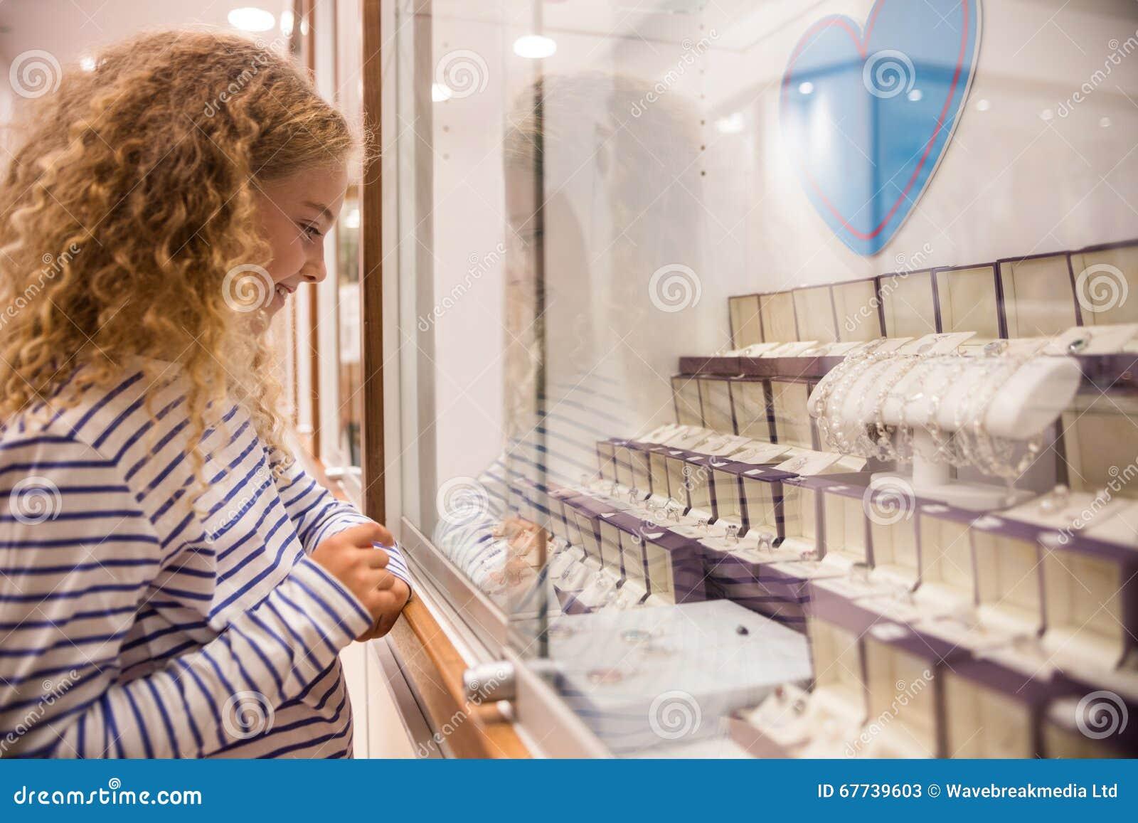 Счастливая девушка смотря дисплей ювелирных изделий
