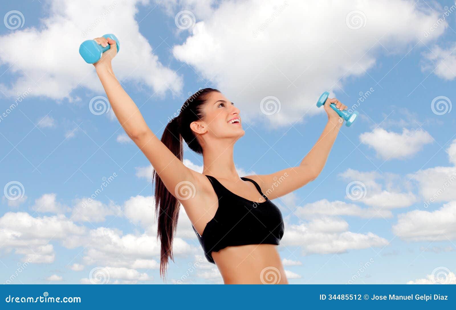 Счастливая женщина брюнет тонизируя ее мышцы