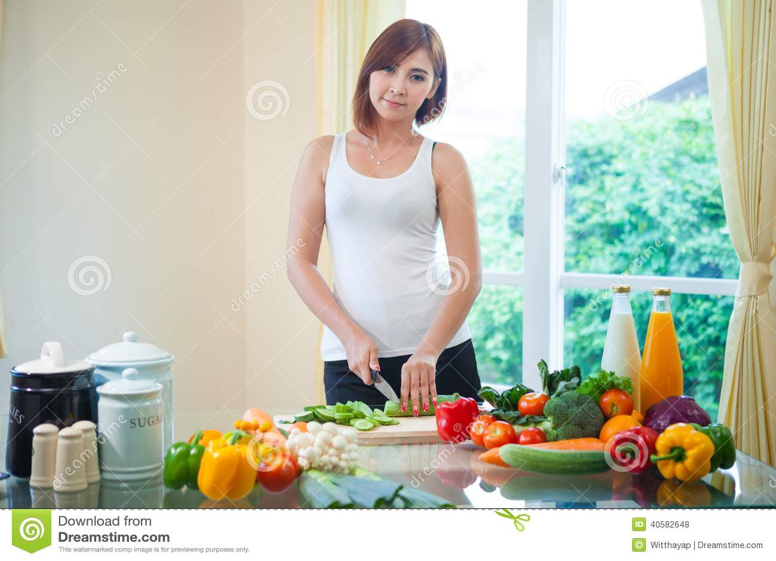 Счастливая женщина варя салат овощей зеленый