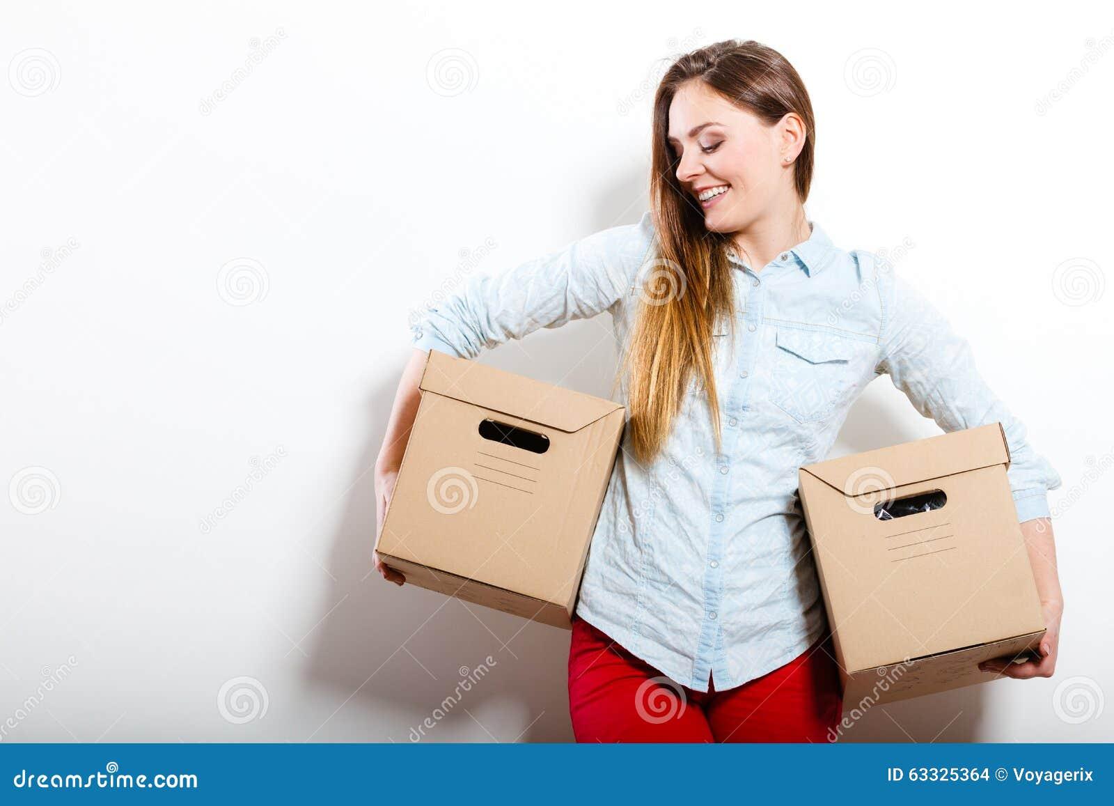 Счастливая женщина двигая в коробки нося дома