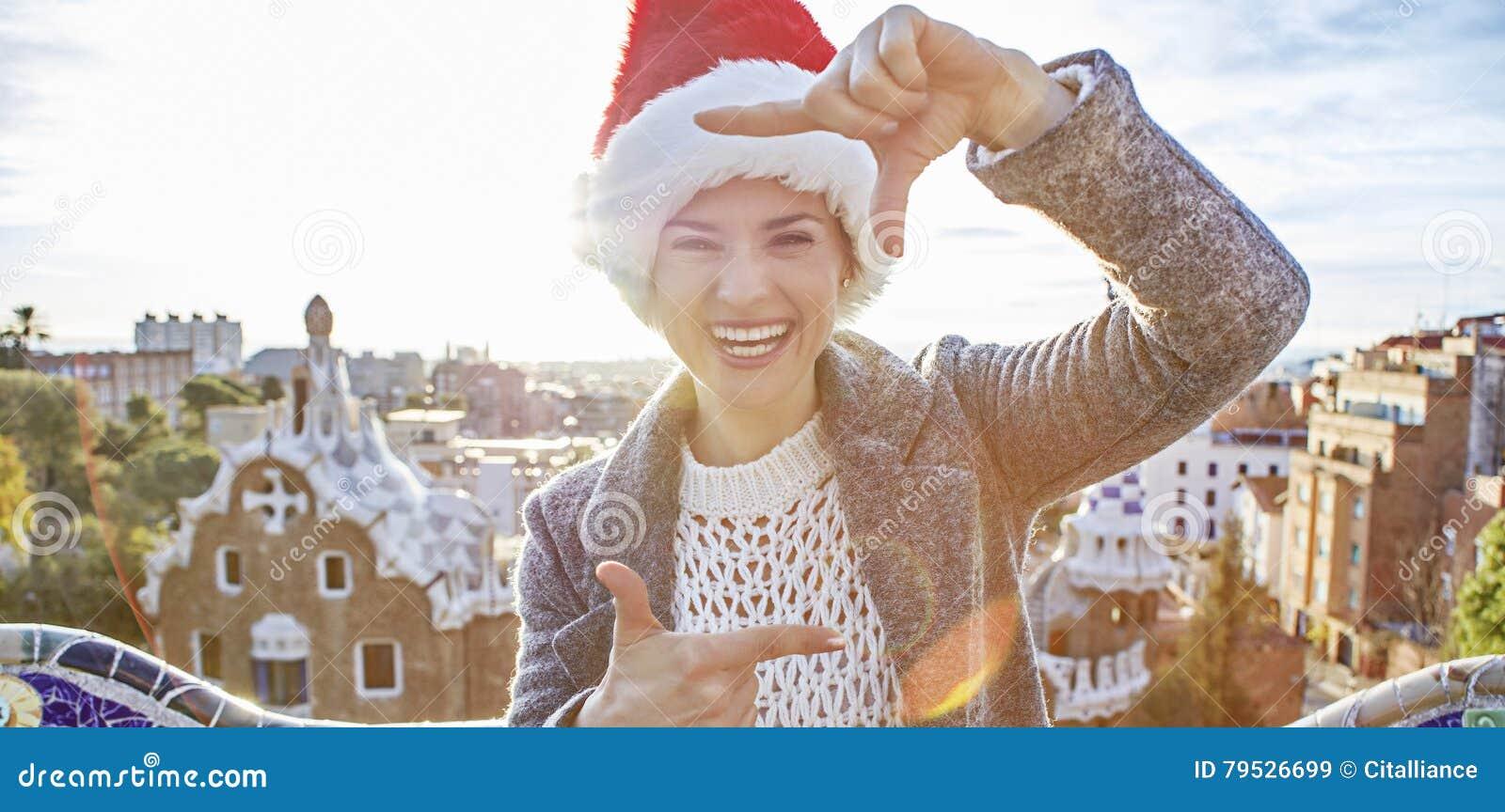 Счастливая женщина в шляпе Санты на парке Guell с обрамлять рук