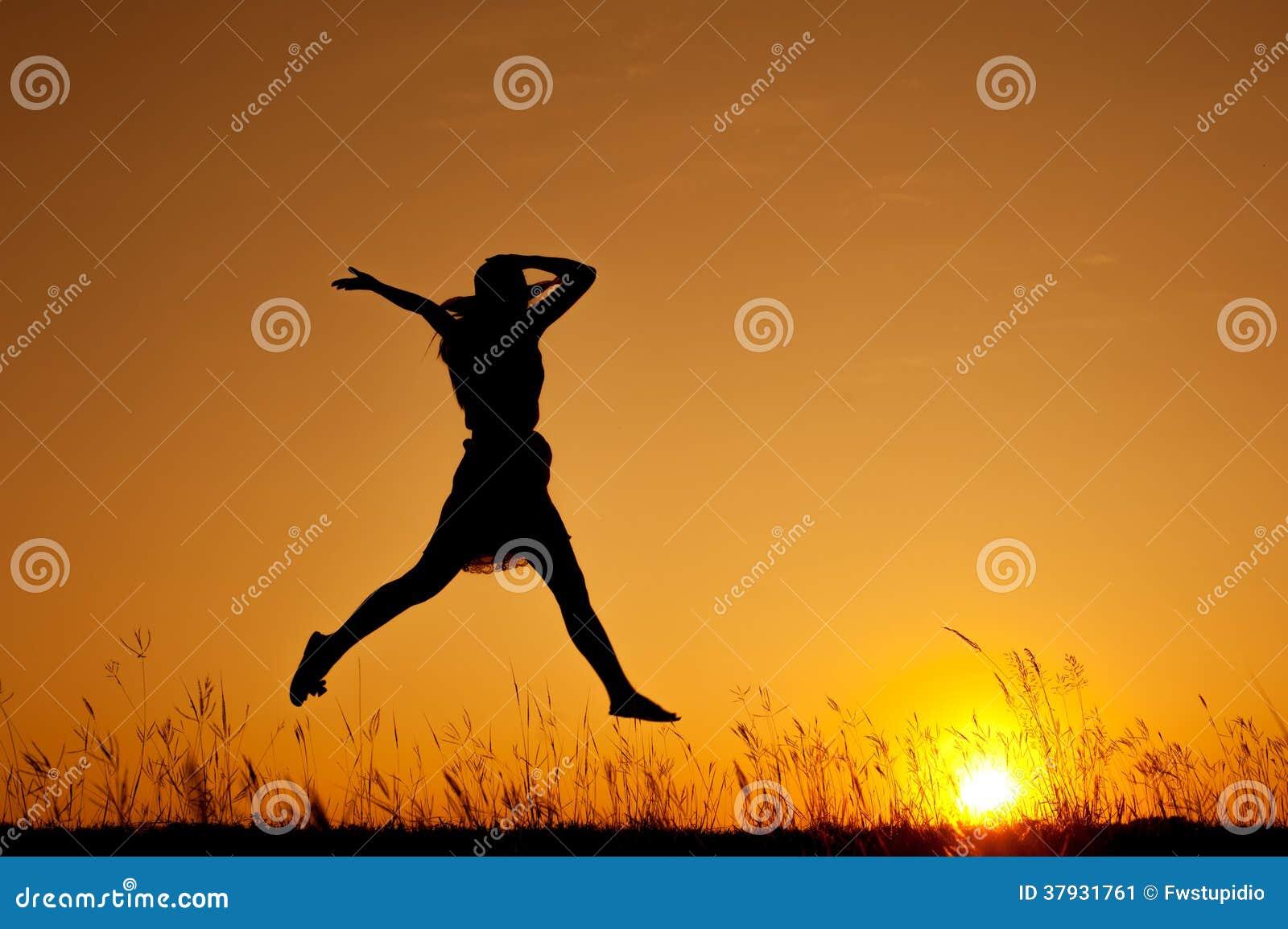 Счастливая женщина и скакать и заход солнца шляпы силуэт