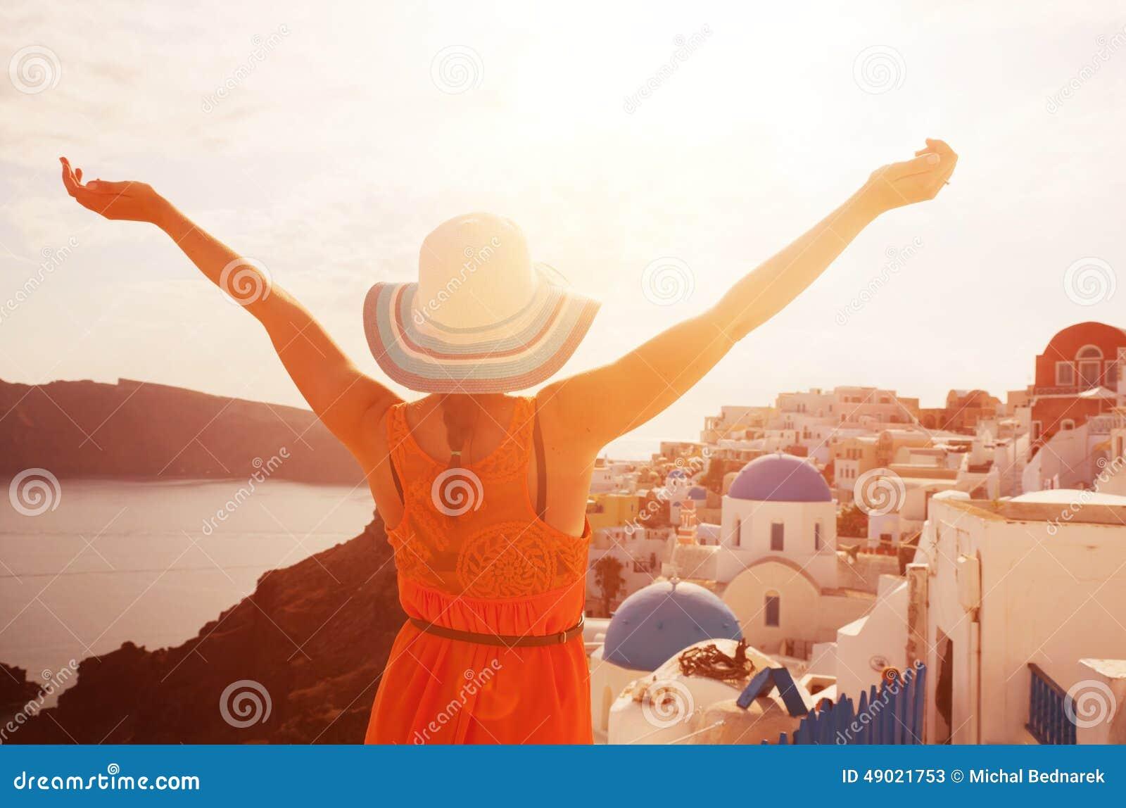 Счастливая женщина наслаждаясь ее праздниками на Santorini, Греции