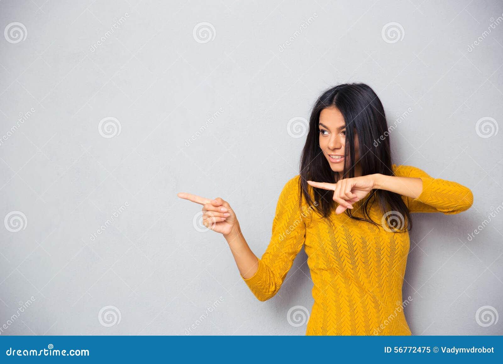 Счастливая женщина показывая палец прочь