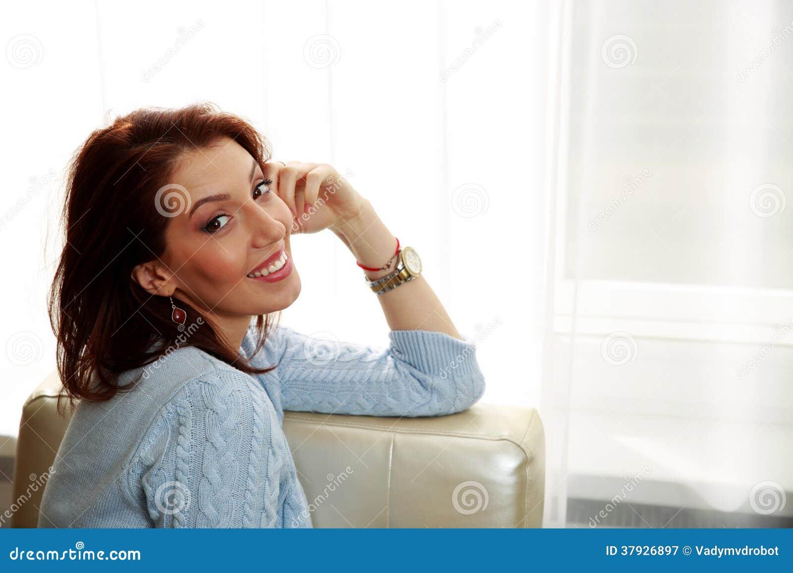 Счастливая женщина сидя на софе