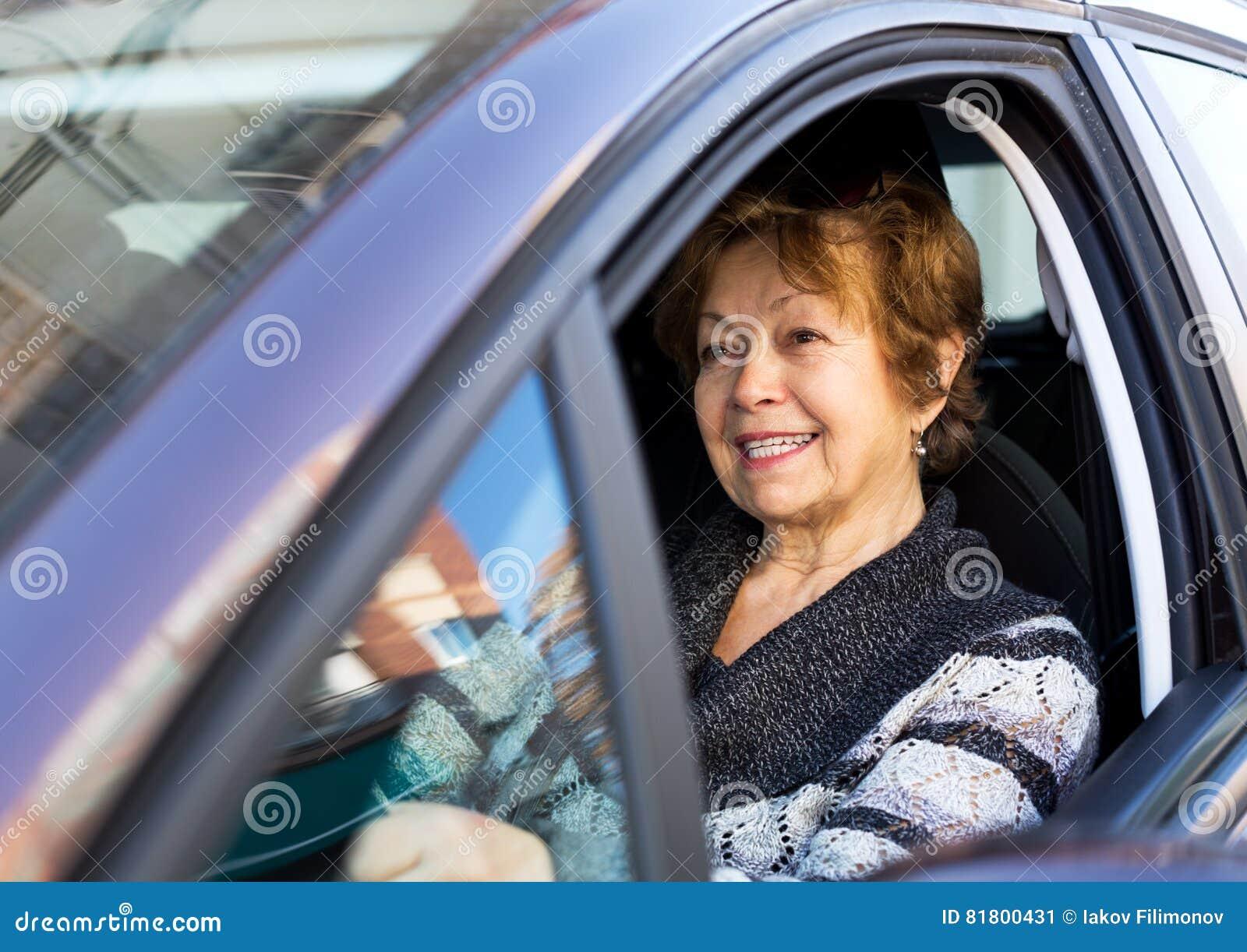 Счастливая зрелая женщина сидя в новом автомобиле