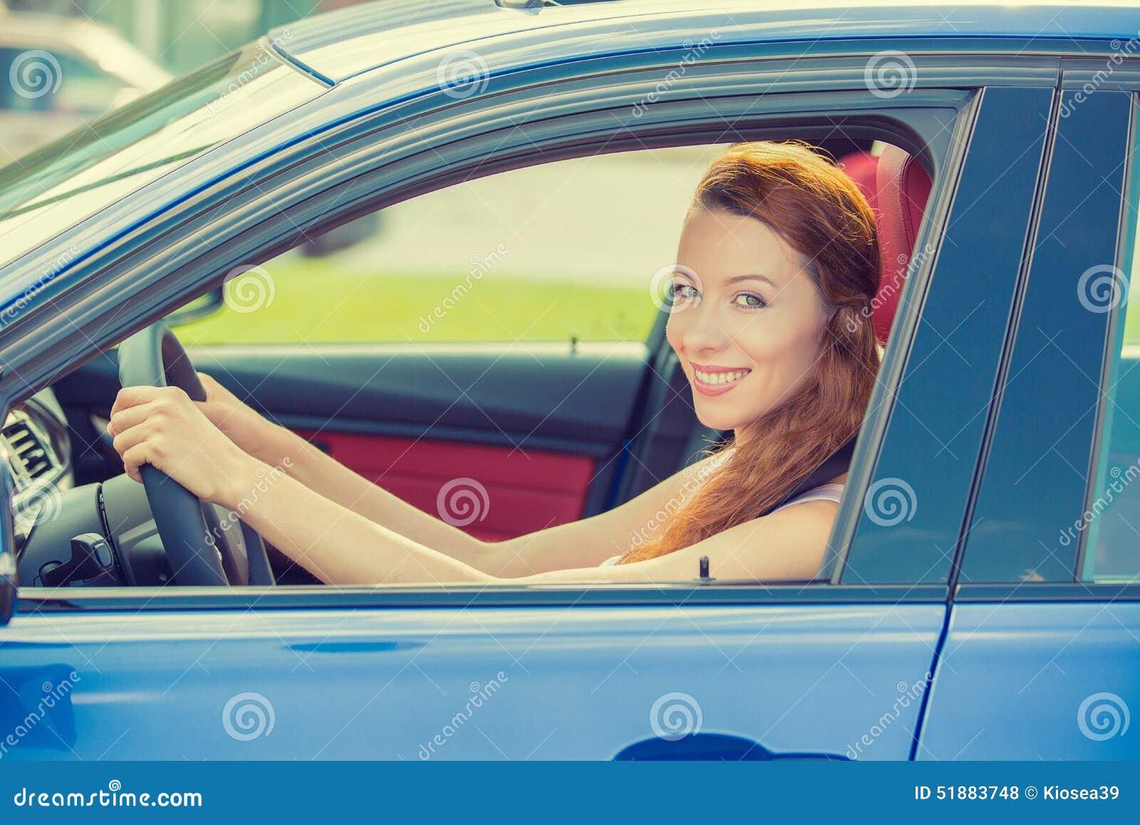 Счастливая красивая молодая женщина управляя ее новым голубым автомобилем