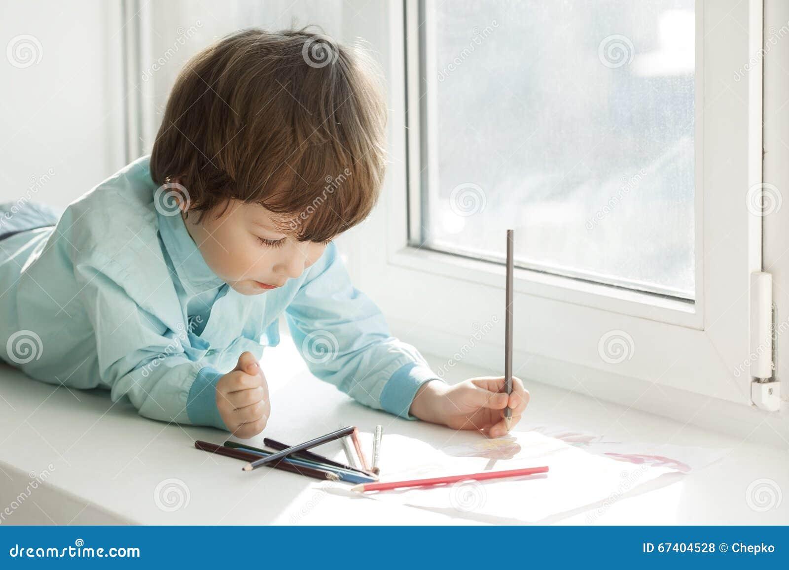 Счастливая краска мальчика на окне