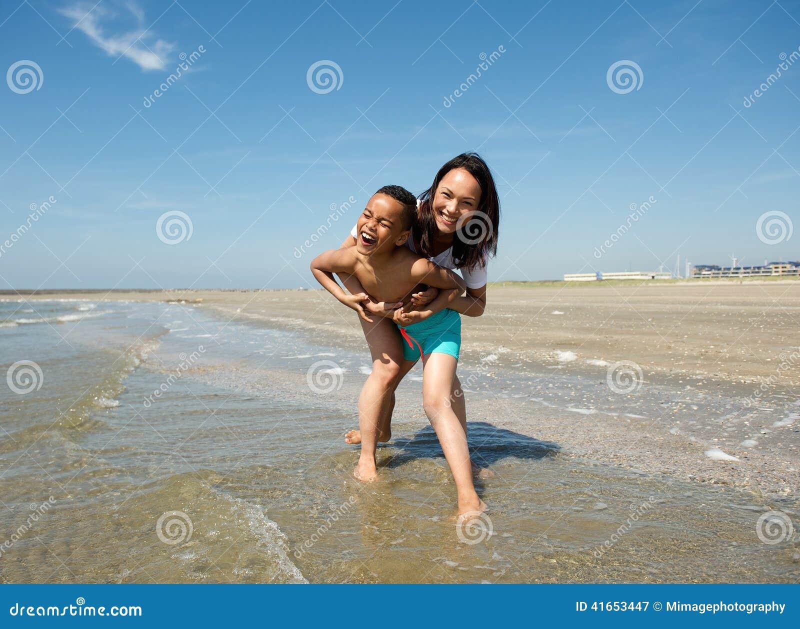 Счастливая мать и сын играя на пляже