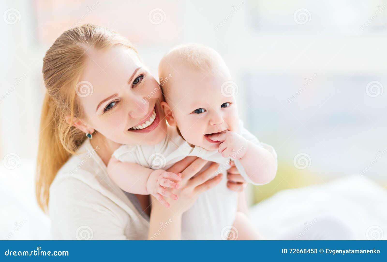 Счастливая мать семьи с играть младенца и объятие в кровати