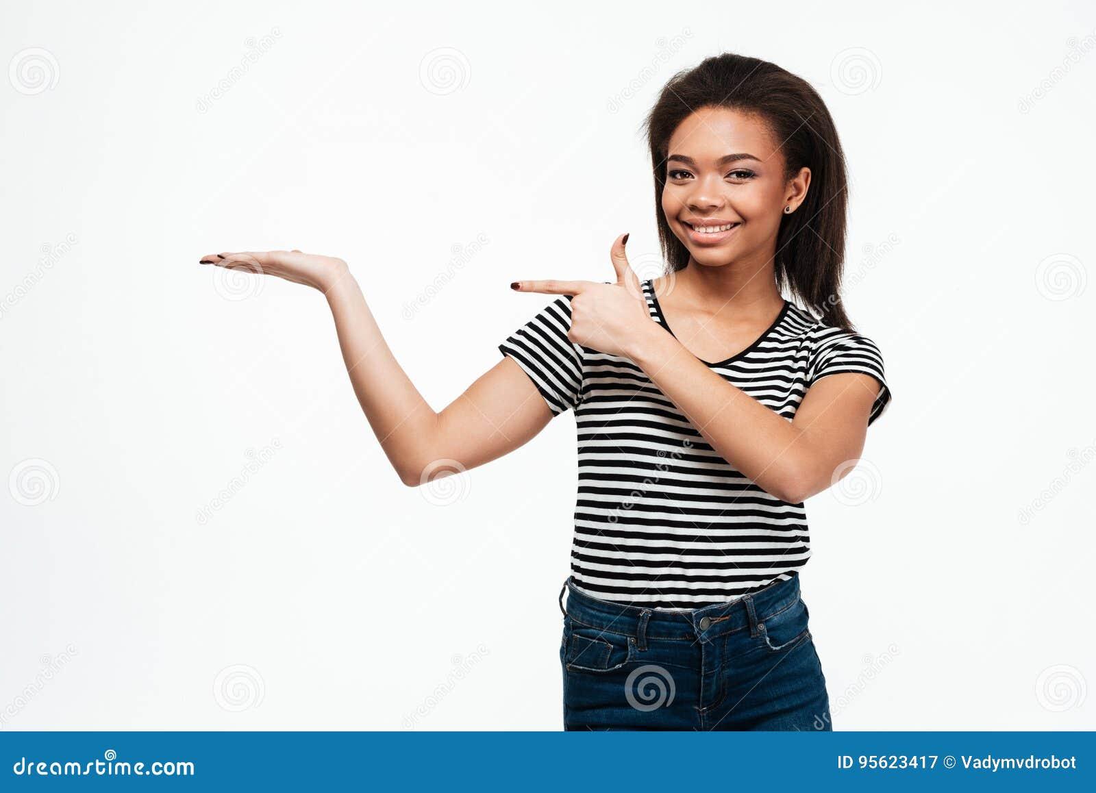Счастливая молодая африканская дама держа copyspace в руке пока указывающ