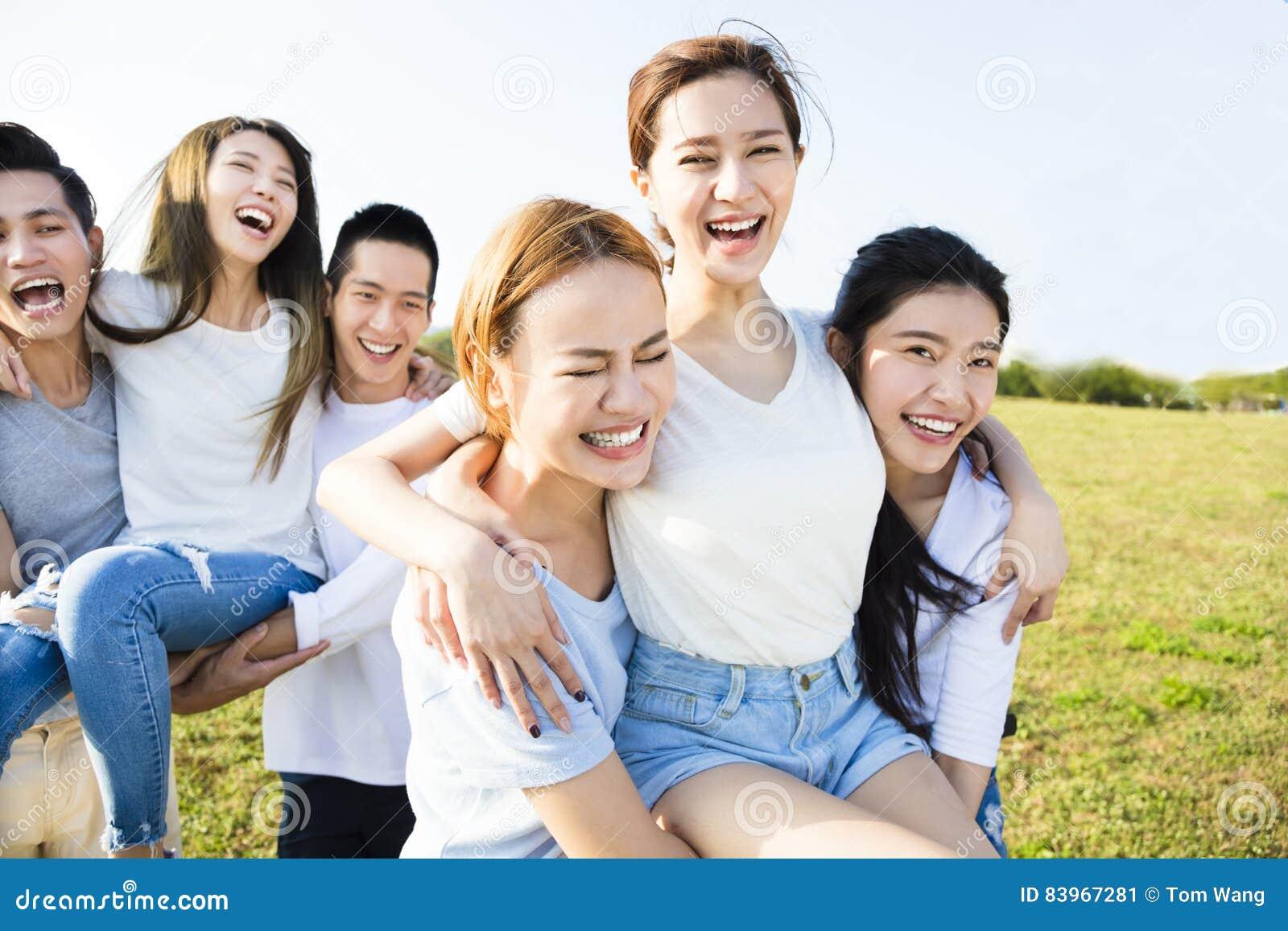 Счастливая молодая группа имея потеху совместно