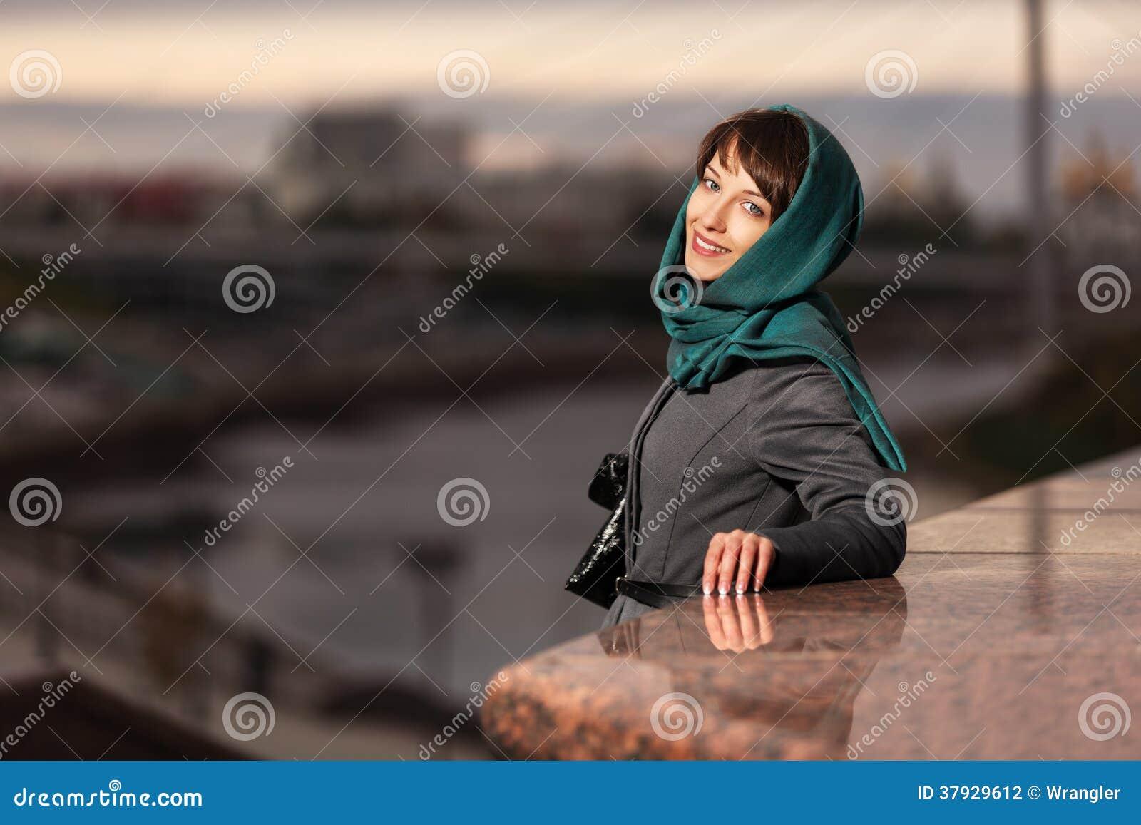 Счастливая молодая женщина в классическом пальто