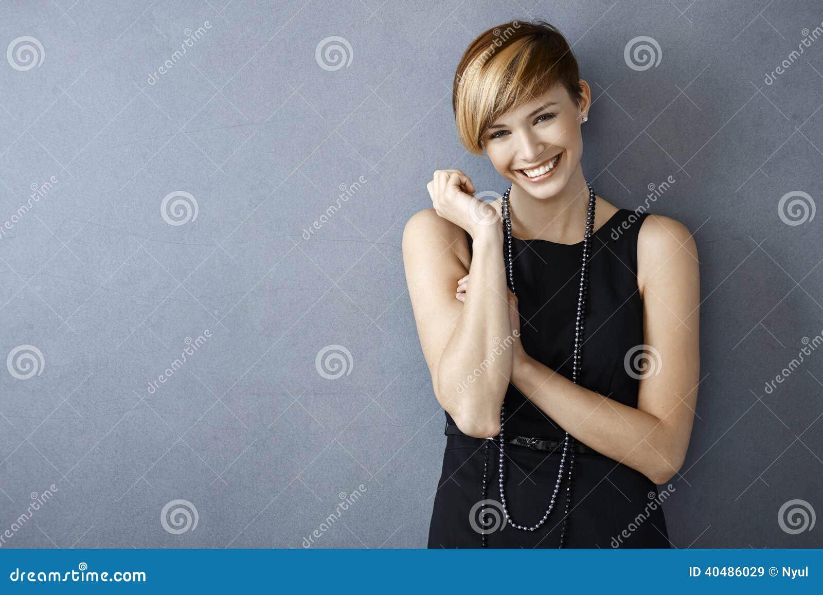 Счастливая молодая женщина в черных платье и жемчугах