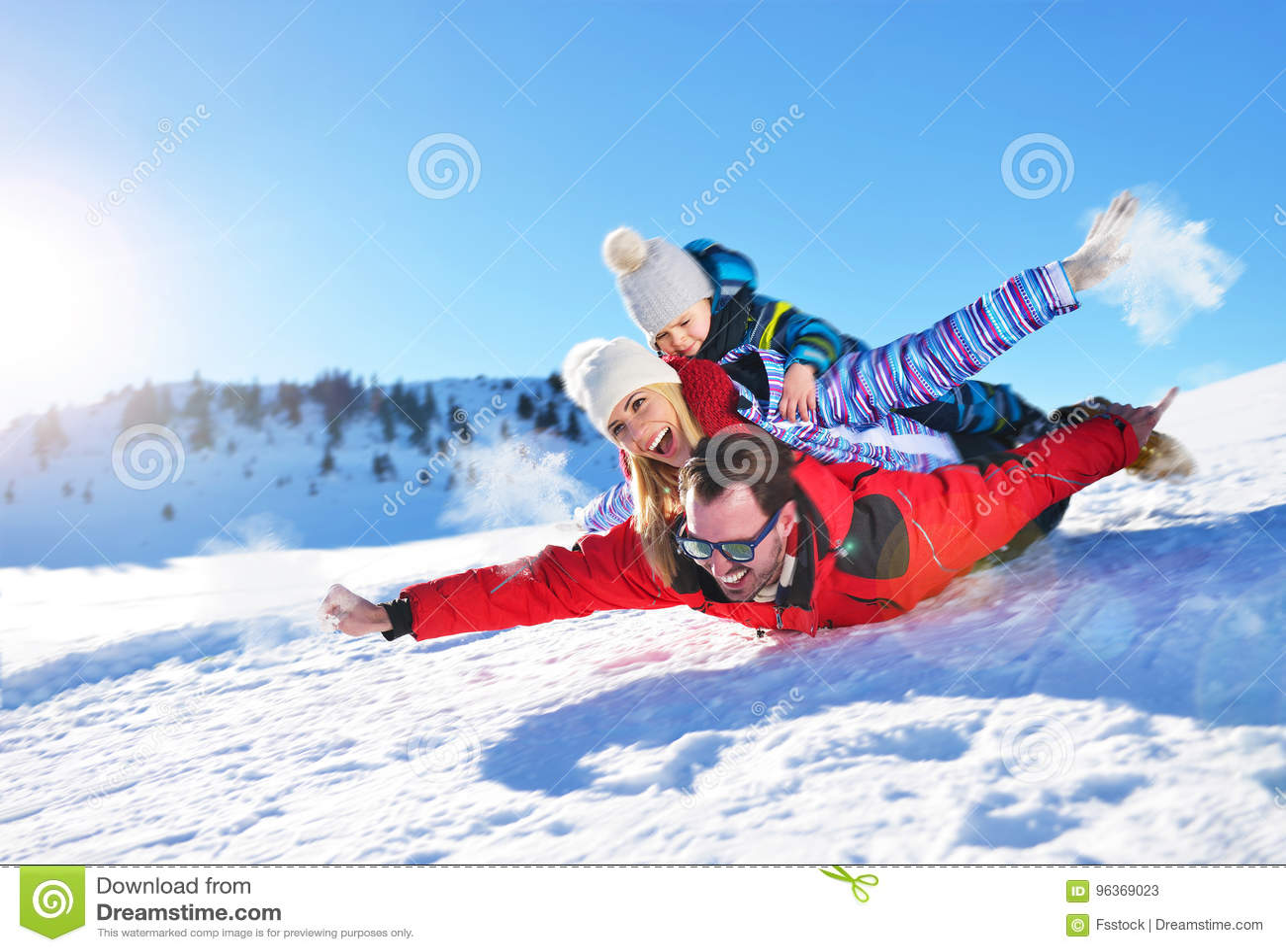 Счастливая молодая семья играя в свежем снеге на красивом солнечном зимнем дне внешнем в природе