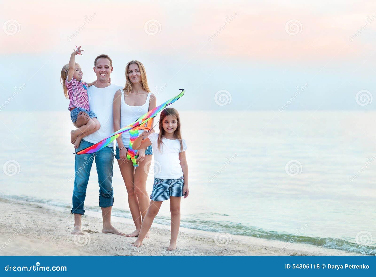 Счастливая молодая семья с летать змей на пляже