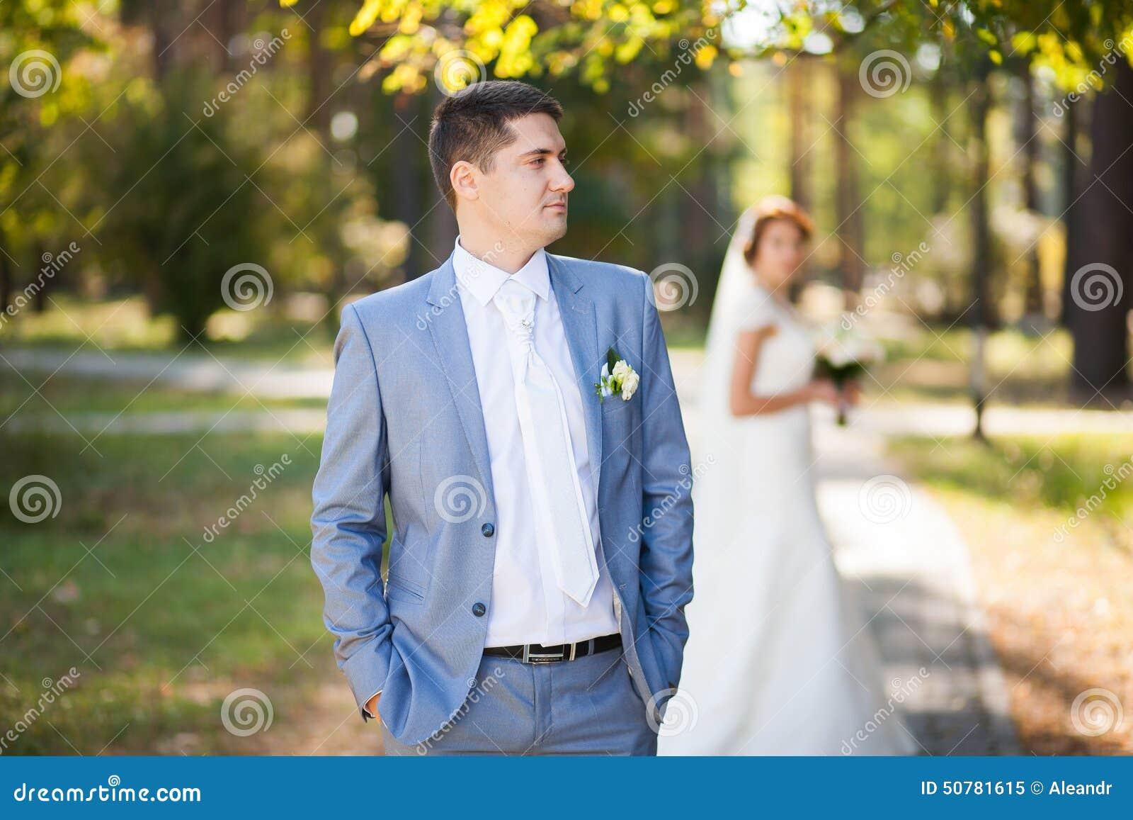 Счастливая невеста, groom стоя в зеленом парке, целующ, усмехающся, смеясь над любовники в дне свадьбы соедините счастливых детен