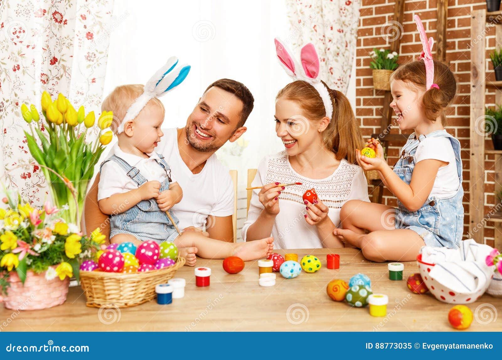 Счастливая пасха! мать, отец и дети семьи красят яичка для