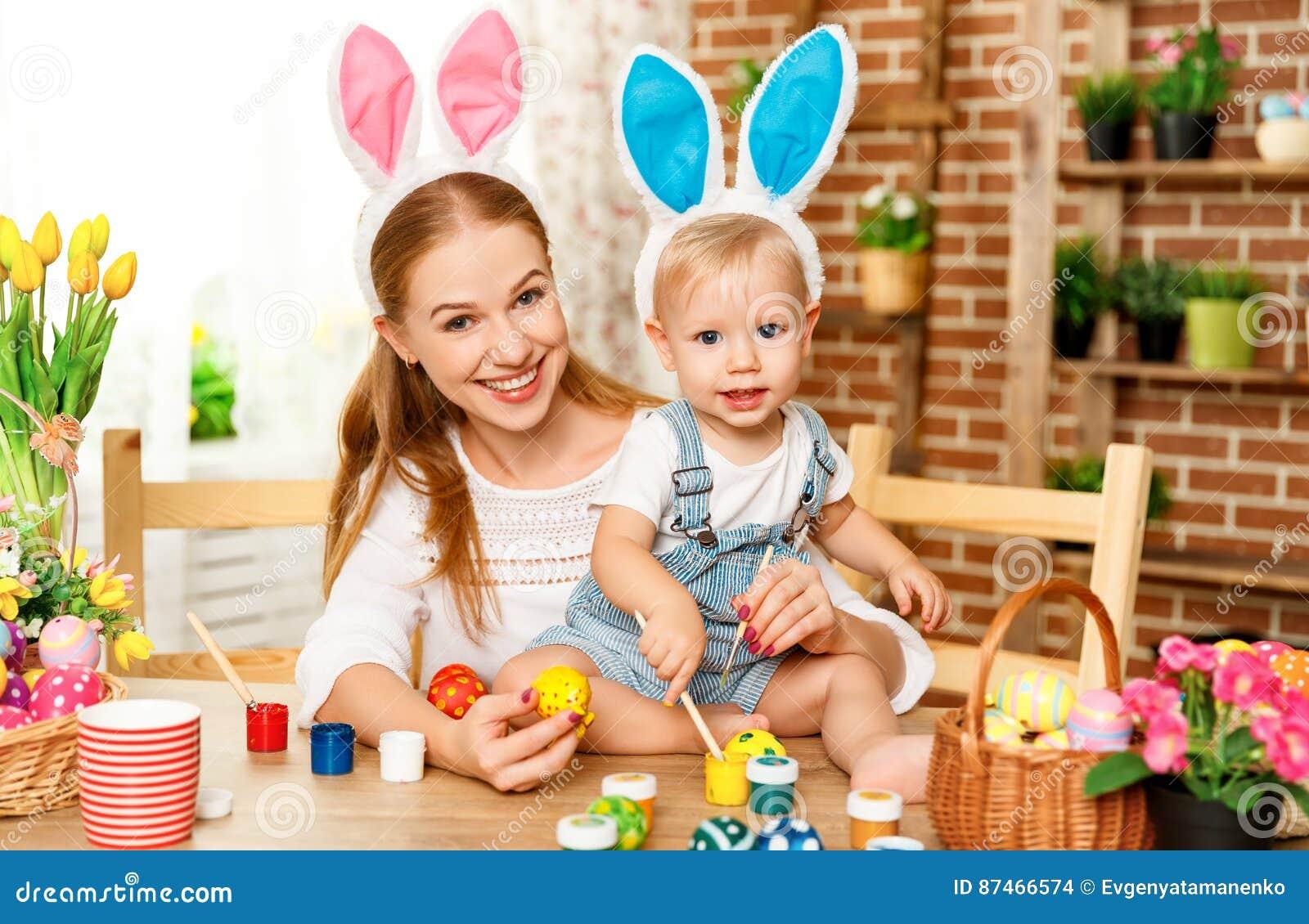 Счастливая пасха! мать семьи и сын младенца красят яичка на праздник