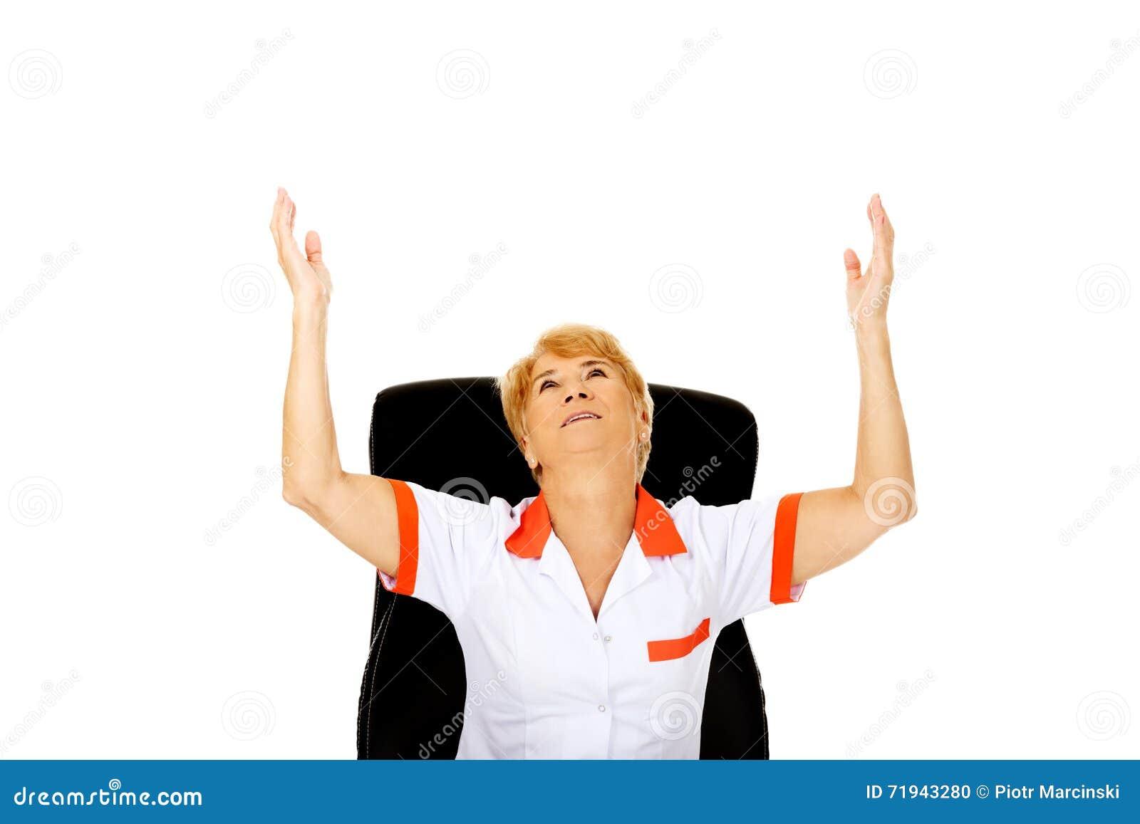 Счастливая пожилая женщина сидя за столом с руками вверх