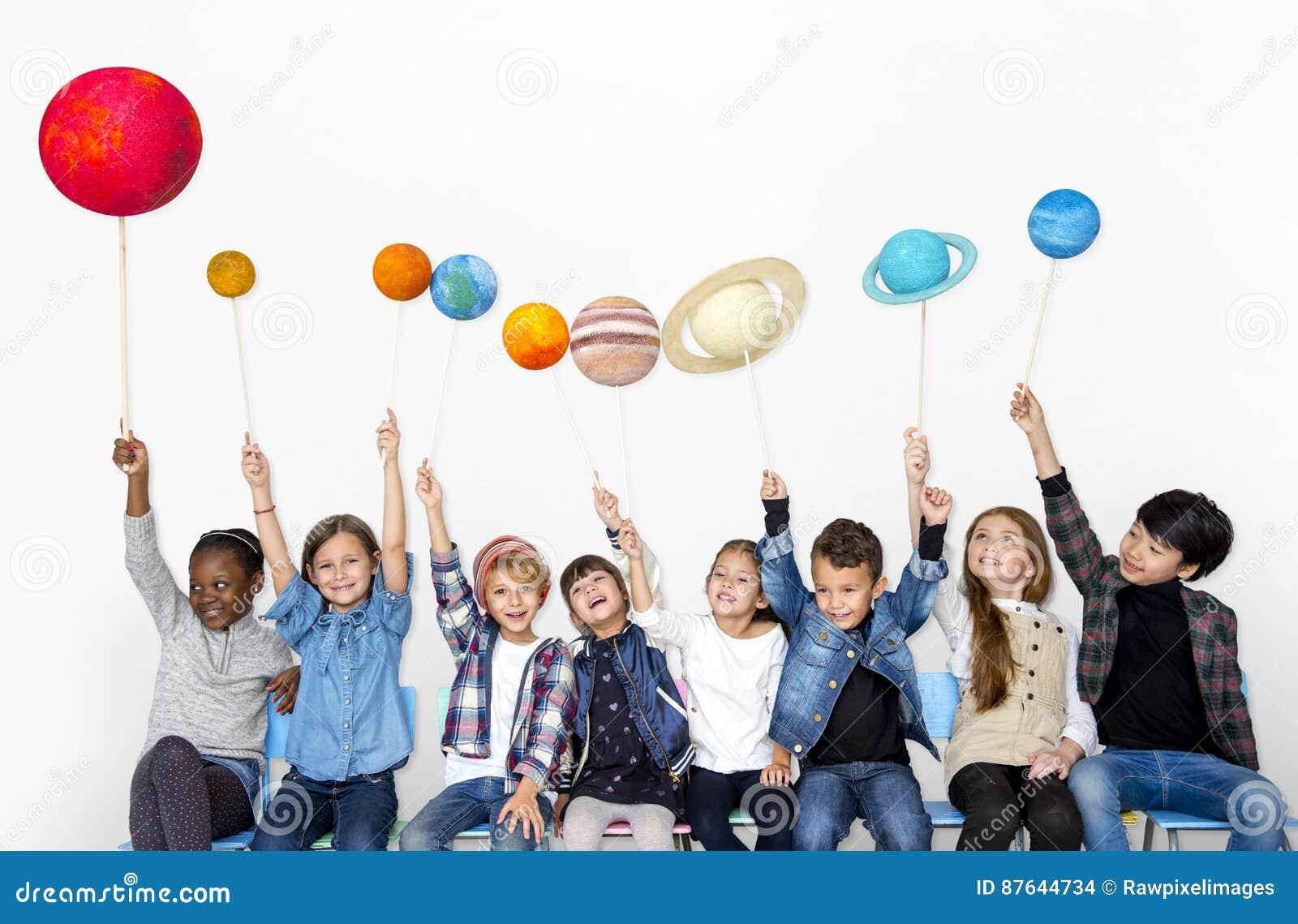Счастливая разнообразная группа в составе дети держа планеты