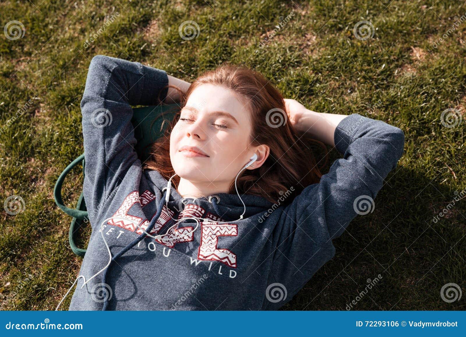 Download Счастливая расслабленная женщина лежа на траве и слушая к музыке Стоковое Фото - изображение насчитывающей природа, green: 72293106