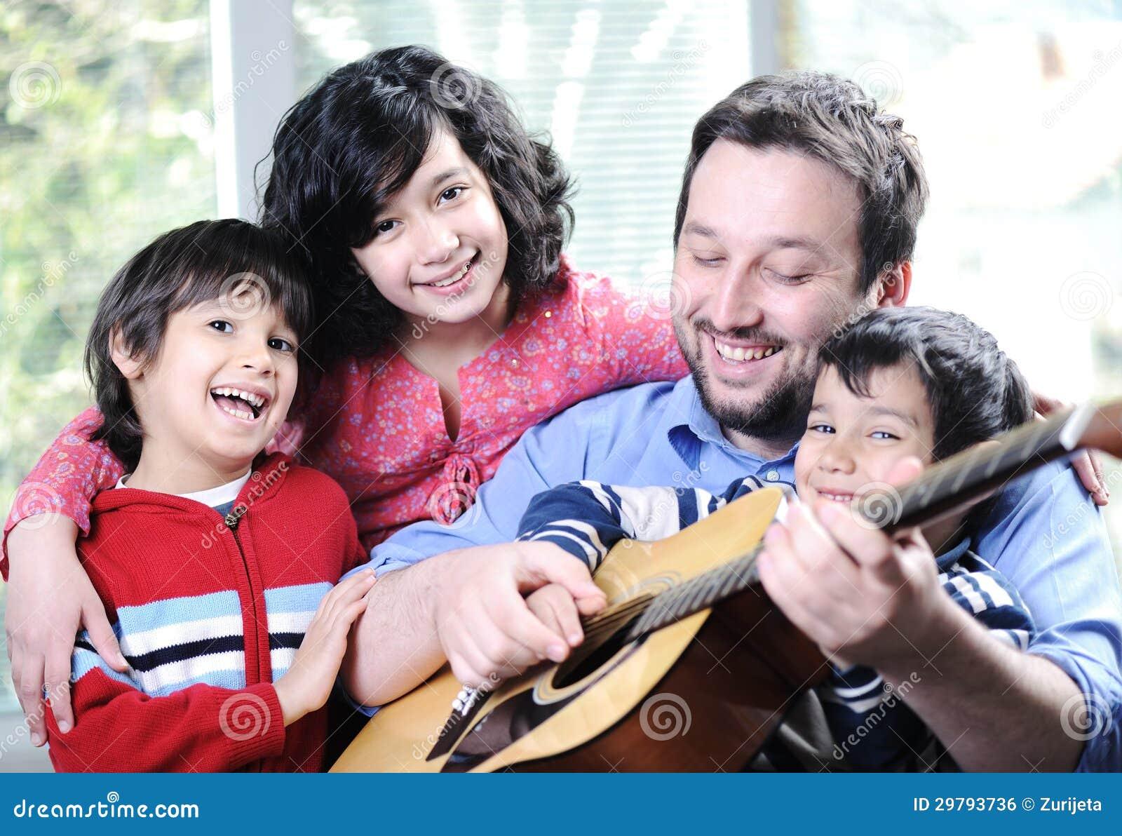 Счастливая семья играя гитару совместно