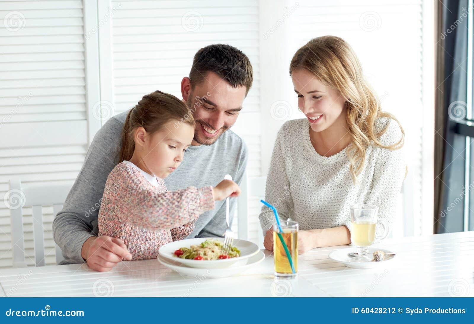 Счастливая семья имея обедающий на ресторане или кафе