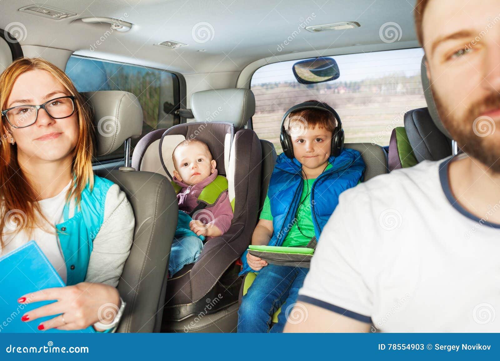 Счастливая семья имея потеху путешествуя автомобилем