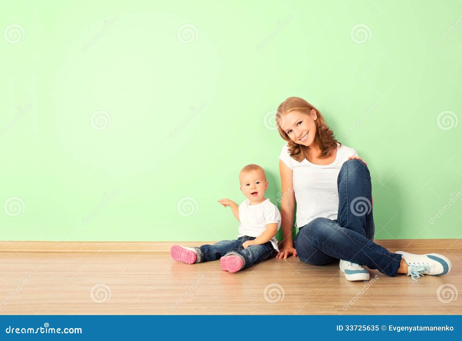 Счастливая семья матери и ребенка сидя на поле в empt