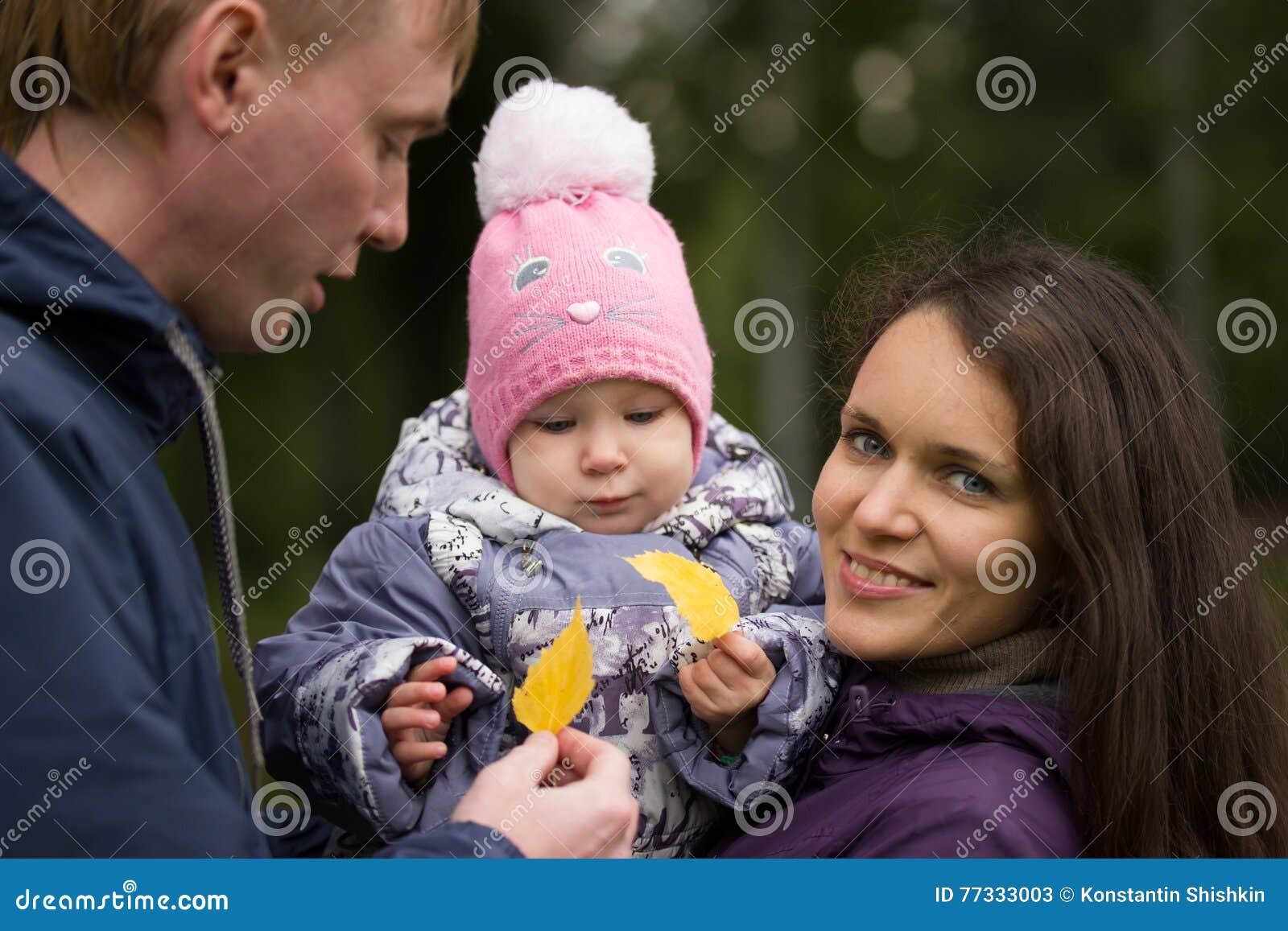 Счастливая семья: Отец, мать и дето- в парке осени: папа, представлять внешний, девушка младенца mammy держа в руках