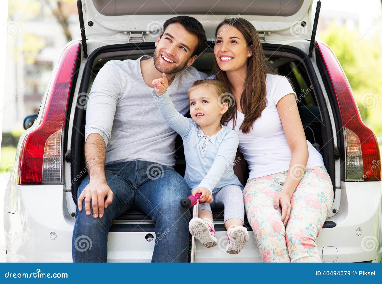 Счастливая семья сидя в автомобиле