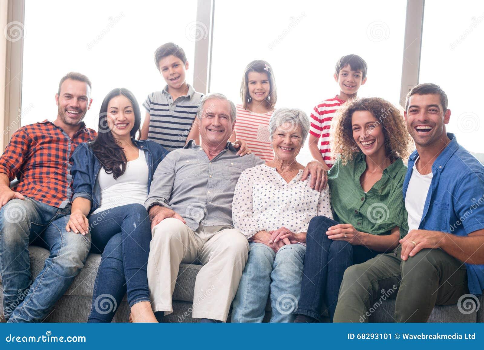 Счастливая семья сидя на софе