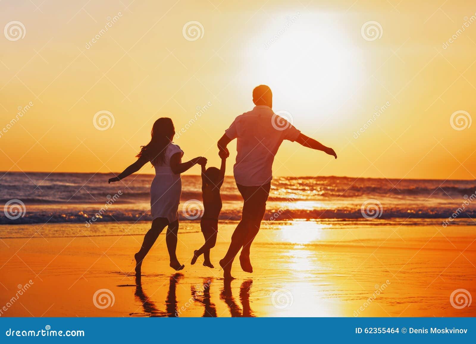 Счастливая семья с ребенком имеет потеху на пляже захода солнца