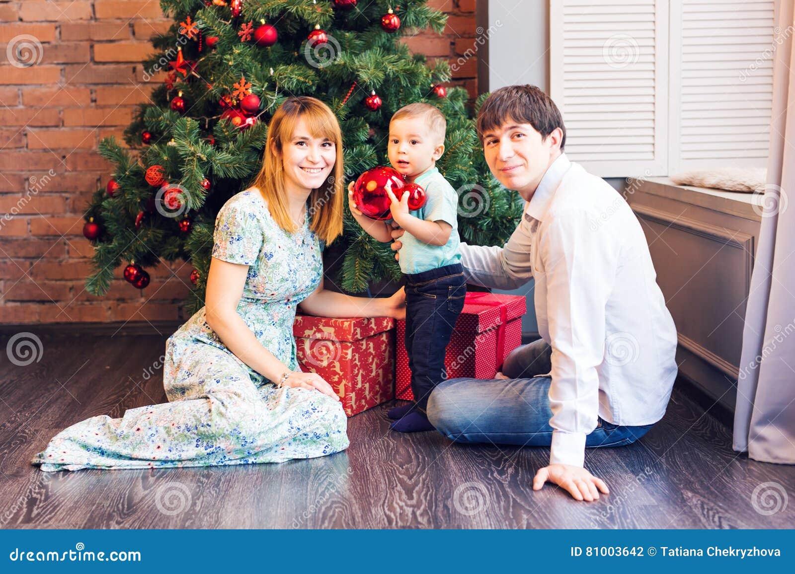 Счастливая семья украшая рождественскую елку совместно Отец, мать и сынок ребенок милый малыш
