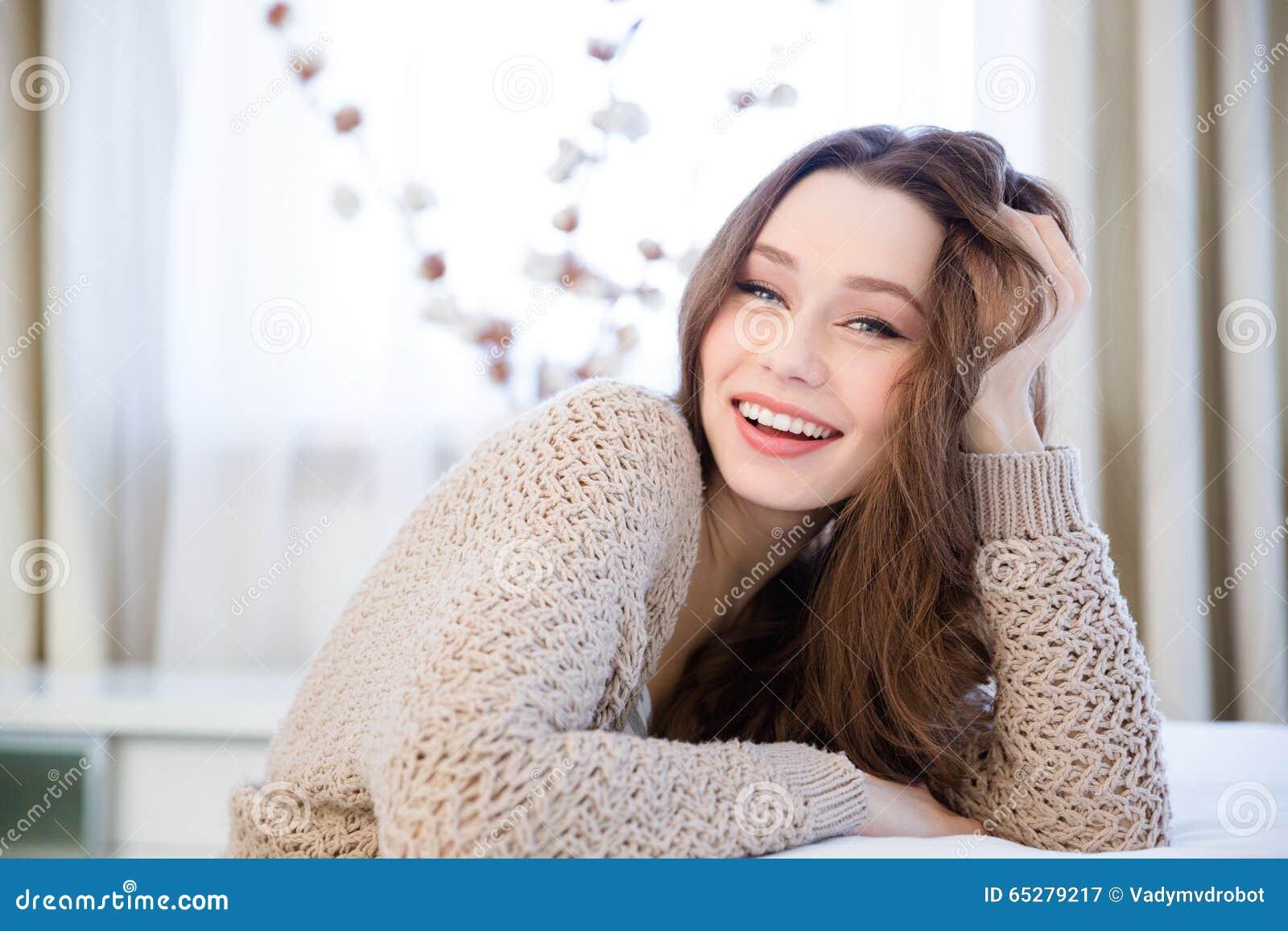 Счастливая симпатичная расслабленная молодая женщина сидя дома