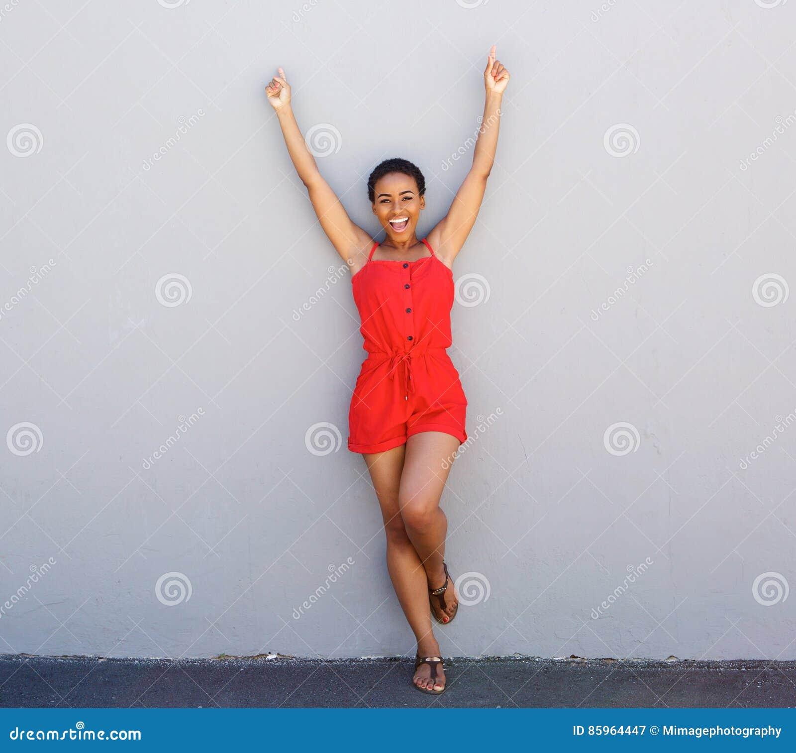 Счастливая склонность молодой женщины против серой стены при поднятые оружия