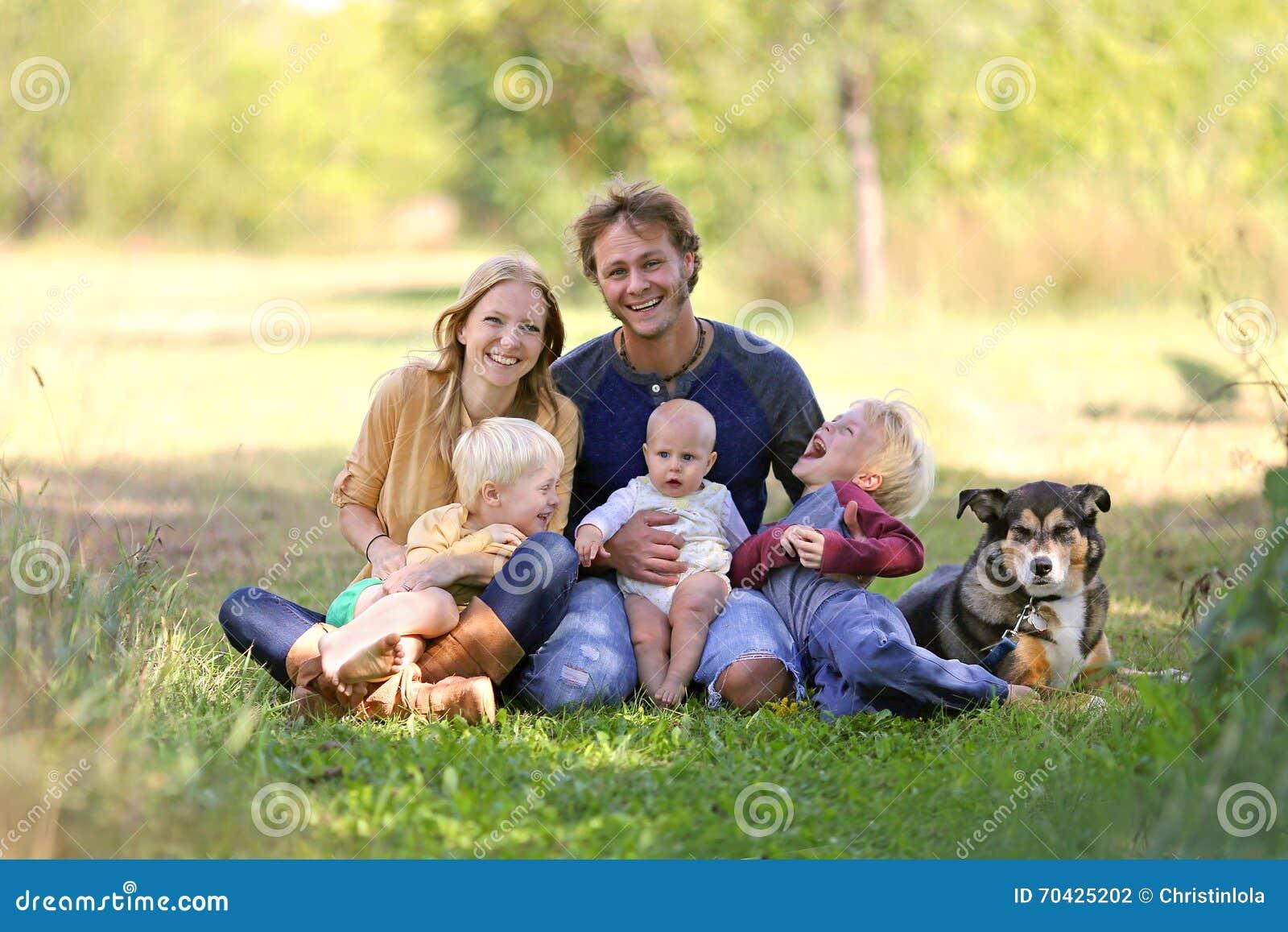 Счастливая смеясь над семья 5 человек и собака в солнечном саде