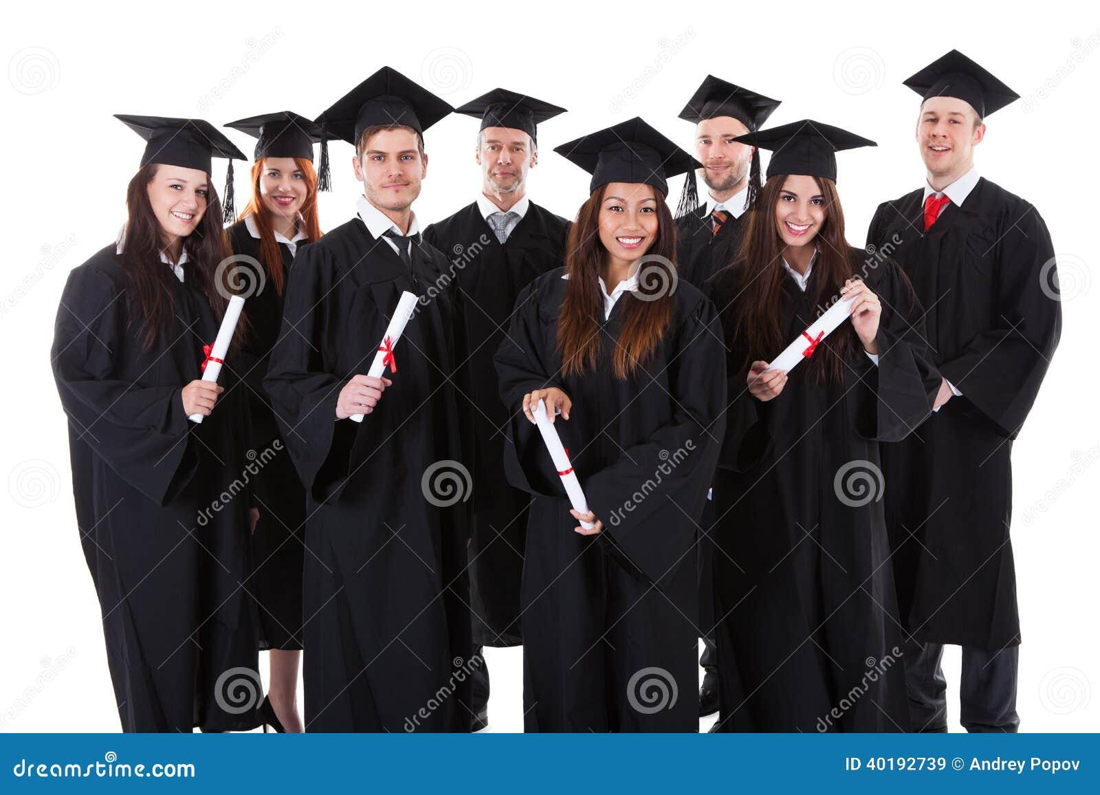 Счастливая усмехаясь группа в составе многонациональные студент-выпускники
