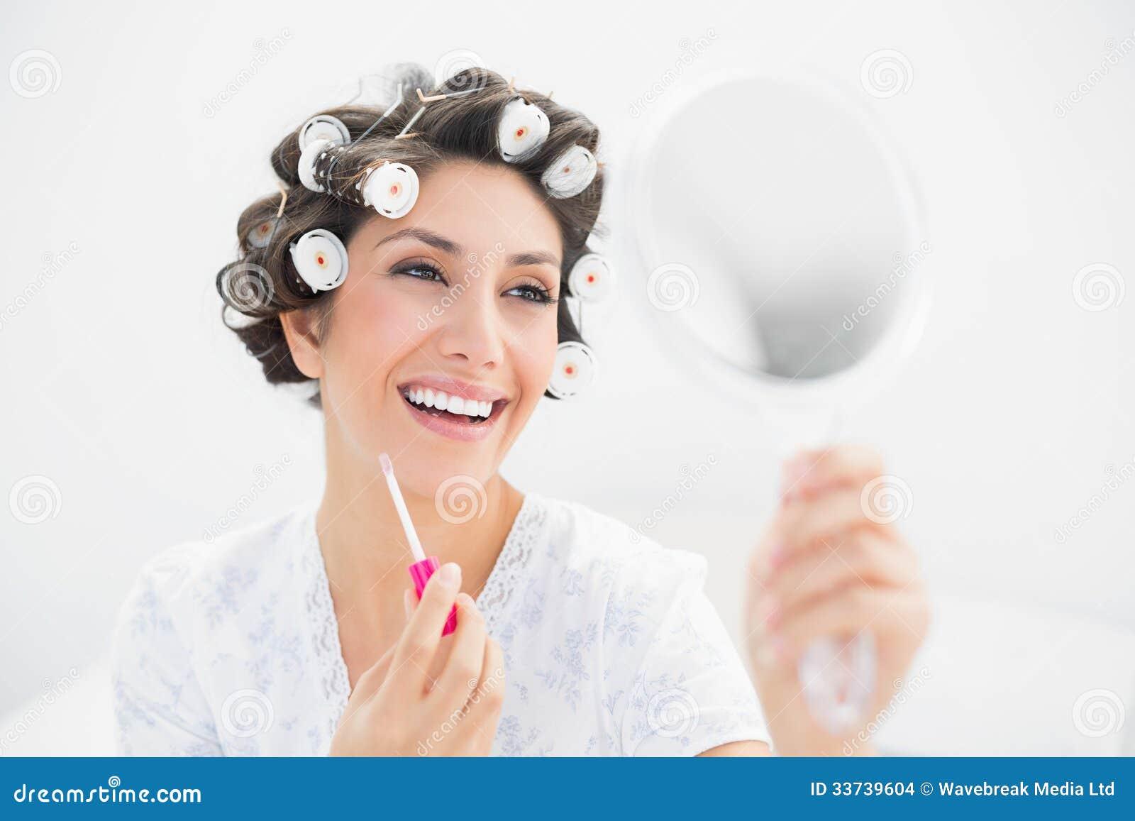 Счастливое брюнет в роликах волос смотря в зеркале руки и держа лоск губы