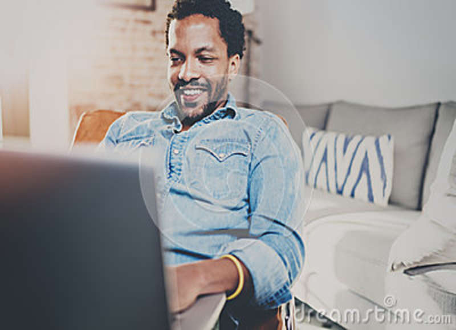 Счастливое молодое бородатое африканское время остатков траты человека дома и использующ компьтер-книжку Концепция людей наслажда