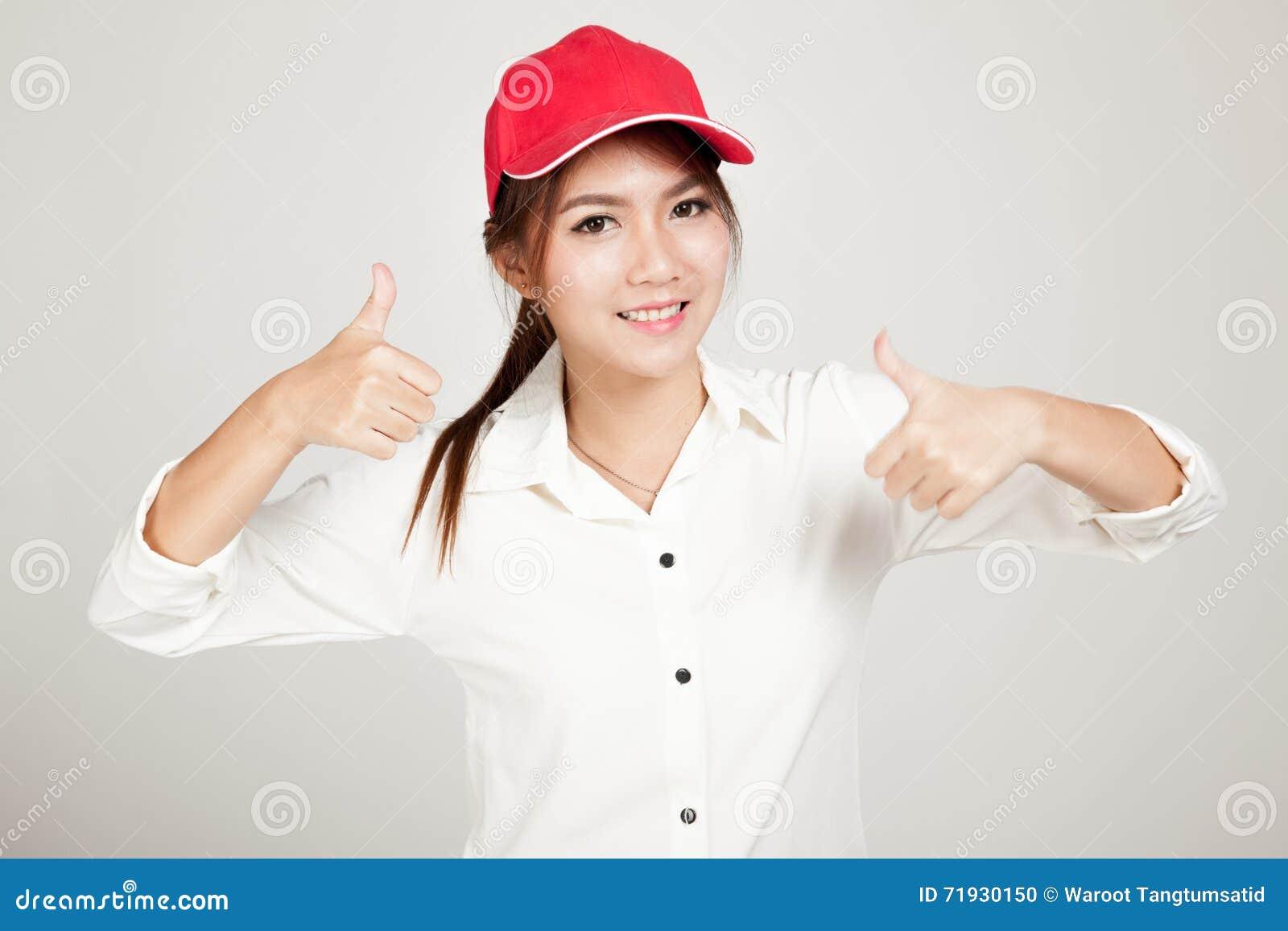 Счастливые азиатские большие пальцы руки девушки вверх с красной шляпой