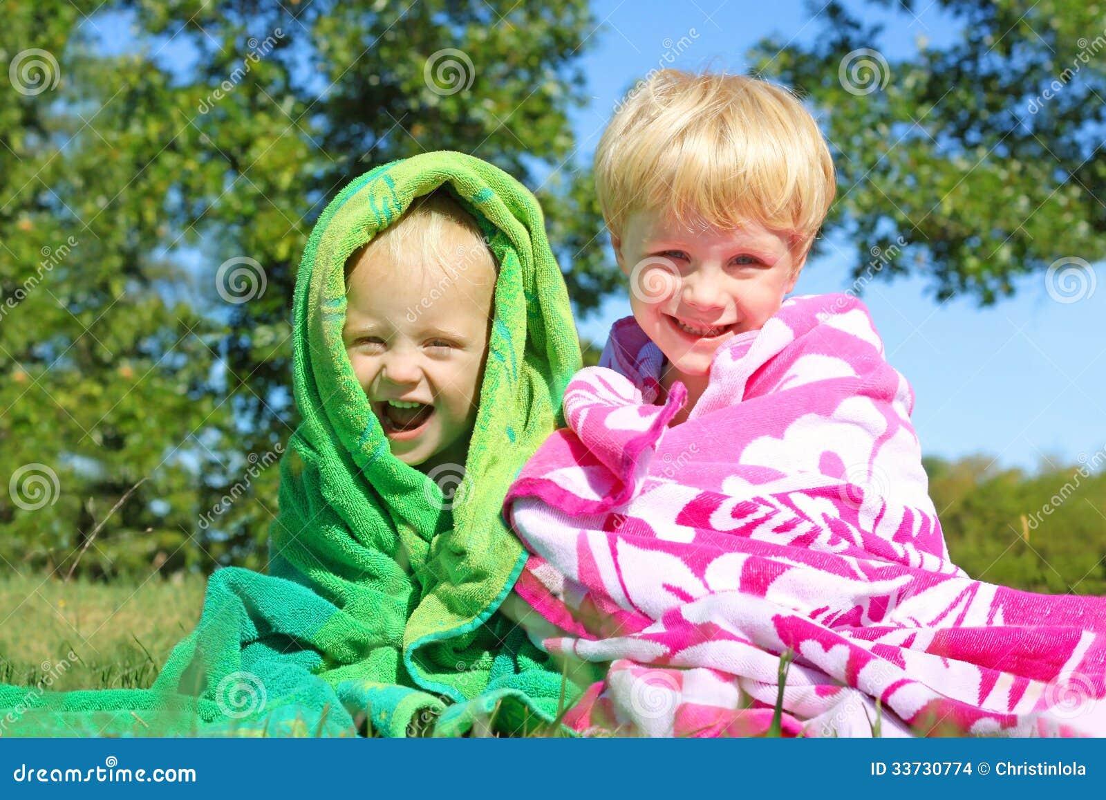 Счастливые братья снаружи в пляжных полотенцах