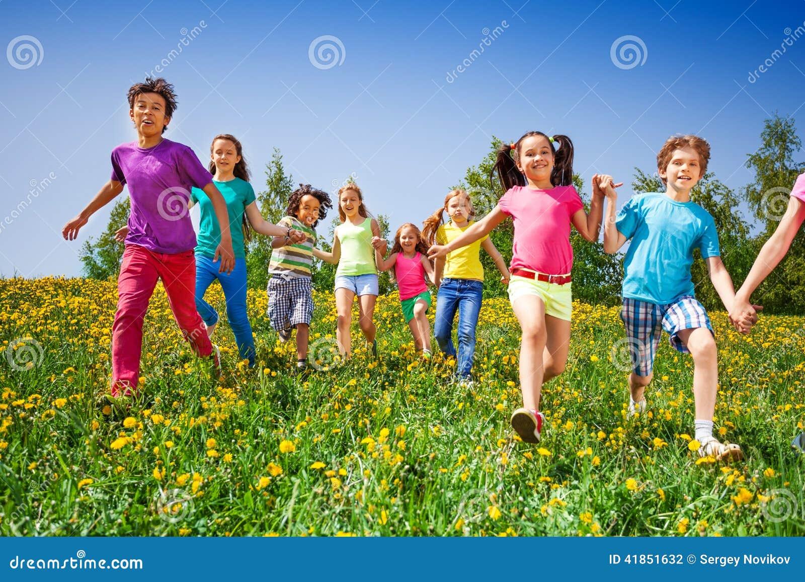 Счастливые дети бегут и держат руки в зеленом луге