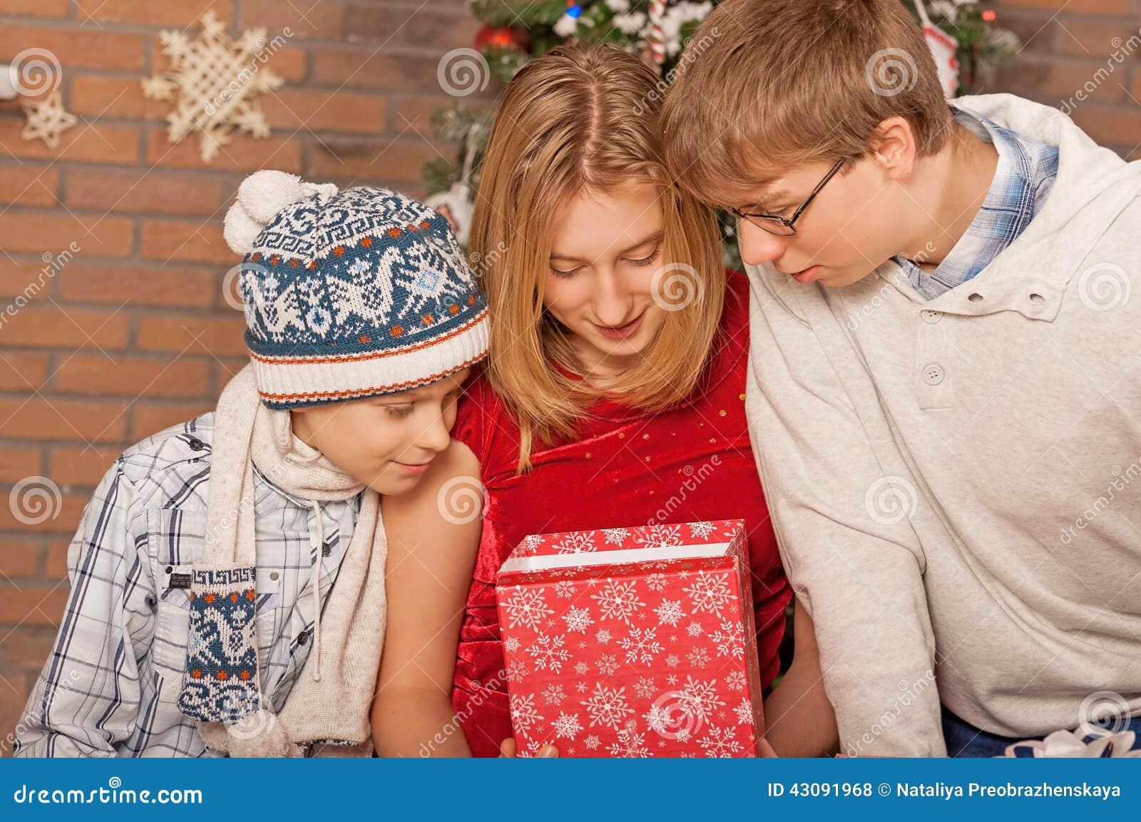 Счастливые дети раскрывая подарки Новый Год