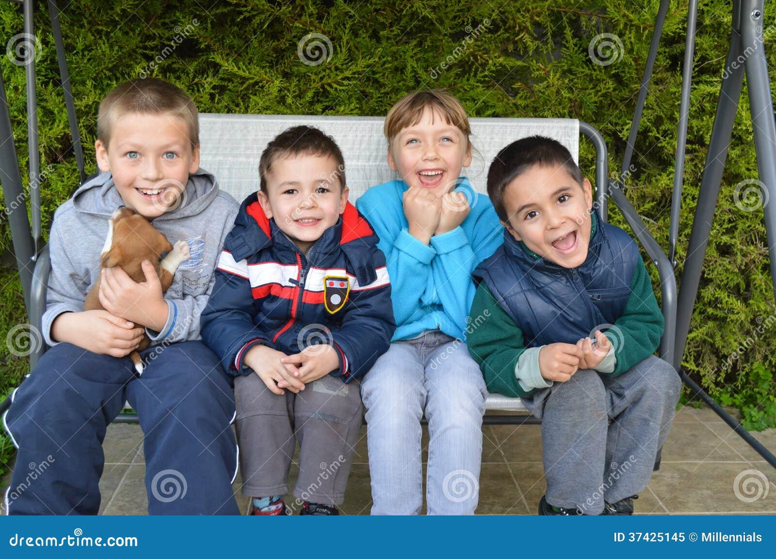 Счастливые дети сидя вместе с щенком