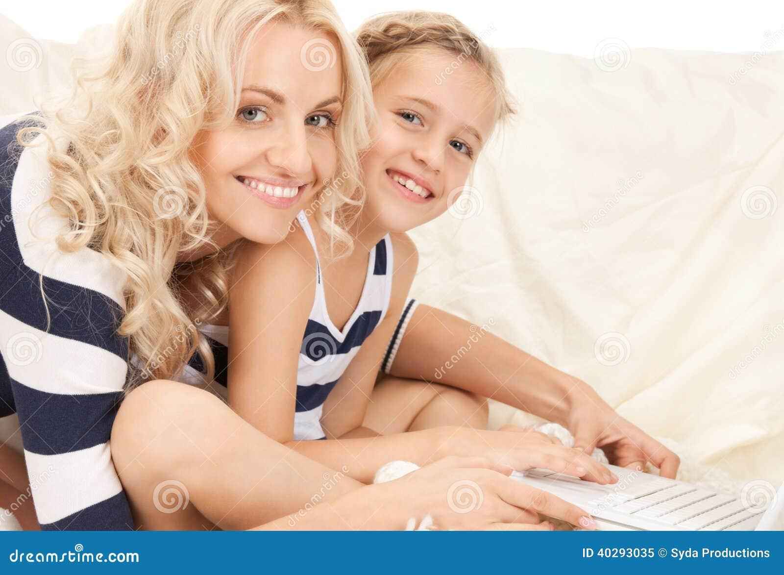 Счастливые мать и ребенок с портативным компьютером